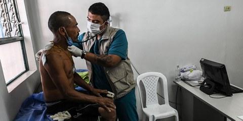 Ungenügend geschützt: Ein Arzt untersucht einen Mann in einer Obdachlosenunterkunft in Medellín. © JOAQUIN SARMIENTO/AFP via Getty Images