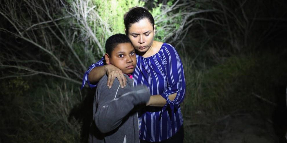 Hunderte von Familien bleiben getrennt. Im Bild: Frau und Kind im Scheinwerferlicht von Beamten nahe der Grenze zwischen den USA und Mexiko. © Getty Images/John Moore