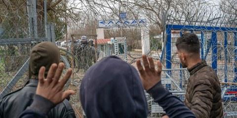 Migranten versuchen mit griechischen Polizeibeamten zu sprechen während der Zusammenstösse an der türkisch-griechischen Grenze in der Nähe von Edirne (Türkei), 4. März 2020 © BULENT KILIC/AFP/Getty Images