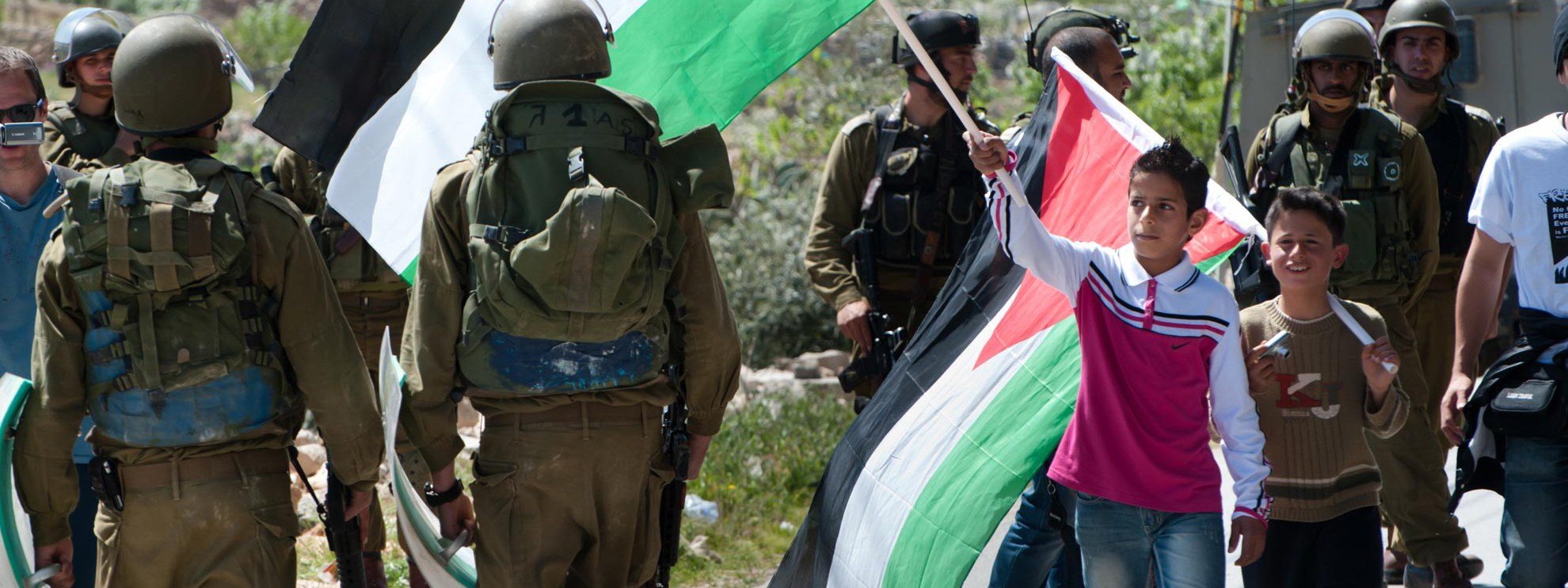 Ein palästinensischer Junge schwingt die palästinensische Fahne vor dem Gesicht eines israelischen Soldaten anlässlich eines Protestmarschs gegen die Trennmauer in Al-Masara. © Ryan Rodrick Beiler / Shutterstock.com