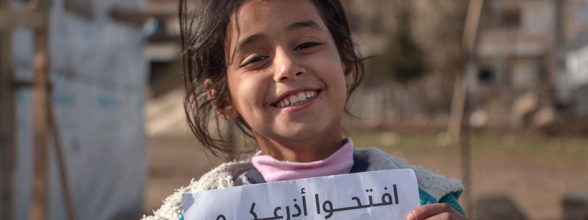 Ein syrisches Flüchtlingskind in einem Lager im Bekaa Tal im Libanon mit einem Schild der Amnesty Kampagne «Open Your Eyes - Open Your Arms - Open your hearts» zur Unterstützung der Flüchtlinge. © Amnesty International
