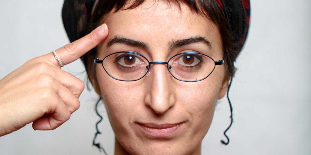 Sewe Karakus zeigt auf ihre Stirn, um zum Nachdenken zu animieren: «Was wäre Ihre positive Botschaft?» © Petar Mitrovic