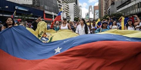 Un drapeau vénézuélien est brandi lors d'une manifestation anti Maduro à Caracas le 23 janvier 2019 © Roman Camacho/SOPA/LightRocket/Getty