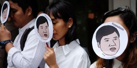 Des membres d'Amnesty International montrent des images de Sirawith «Ja New» Seritiwat, qui a été battu par des inconnus, lors d'une manifestation à Bangkok contre l'attaque du 3 juillet 2019. © Candida Ng/AFP (via Getty Images)