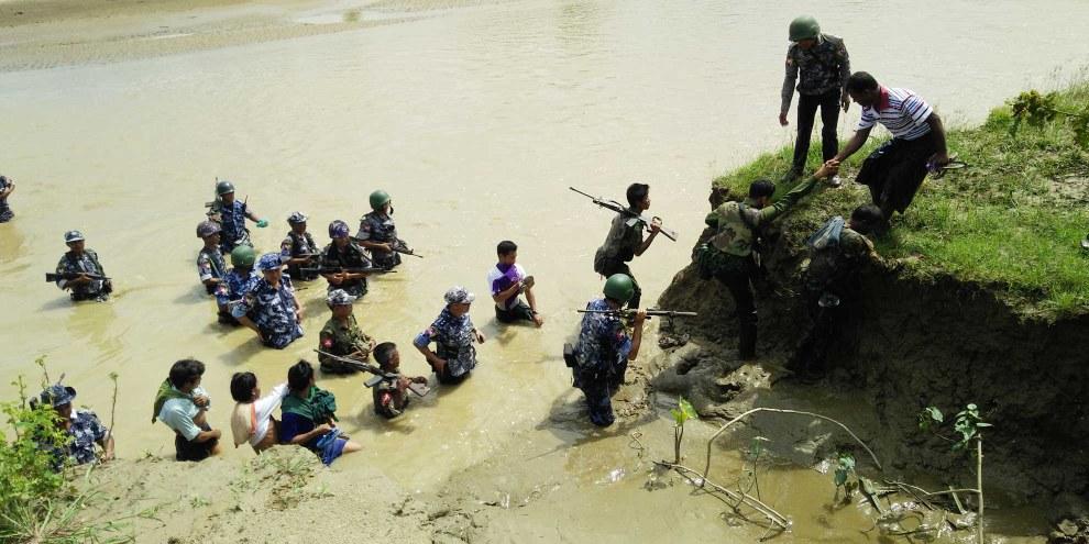 Les forces de sécurité du Myanmar accompagnent les villageois hindous jusqu'aux fosses communes où leurs proches ont été enterrés. Les corps de 45 personnes de Ah Nauk Nauk Kha Maung Maung Seik (canton de Maungdaw, État de Rakhine) ont été déterrés dans quatre fosses communes à la fin septembre 2017. Les victimes font partie des 100 personnes tuées lors de deux massacres perpétrés par l'Armée du Salut des Rohingya de l'Arakan (ARSA) le 25 août 2017. © DR