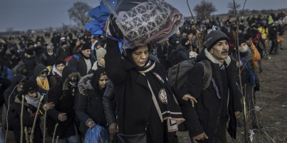Des migrantes et migrants en situation irrégulière se rassemblent à la frontière gréco-turque, dans le quartier de Karaagac à Edirne, en Turquie, pour atteindre la Grèce, le 1er mars 2020. © Arif Hudaverdi Yaman/Anadolu Agency via Getty Images