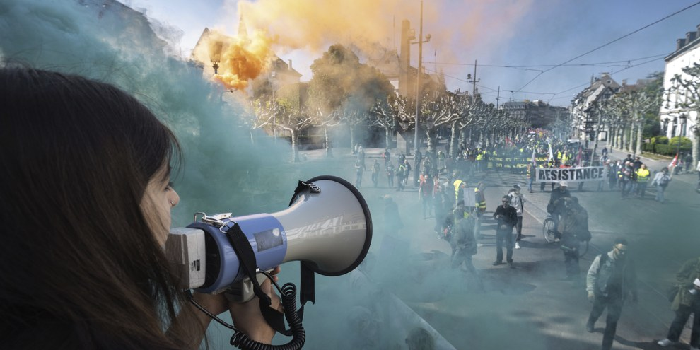 Un manifestant parle à travers un mégaphone alors que de la fumée de fumigènes s'élève près des personnes participant au rassemblement annuel du 1er mai à Strasbourg, dans l'est de la France, le 1er mai 2019. © PATRICK HERTZOG/AFP via Getty Images