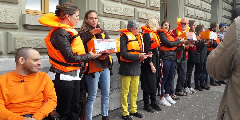"""De plus en plus de vies sont aujourd'hui perdues parce que les gouvernements bloquent l'Aquarius. Remise des 25'000 signatures pour la pétition'Pavillon suisse pour le navire auxiliaire """"Aquarius"""" le 9 octobre.  © Gerard Bottino / shutterstock.com"""