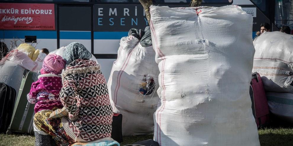 Une femme et son enfant en train d'attendre le bus. Il les mènera jusqu'à Kilis, près de la frontière avec la Syrie. © SOPA/Getty Images
