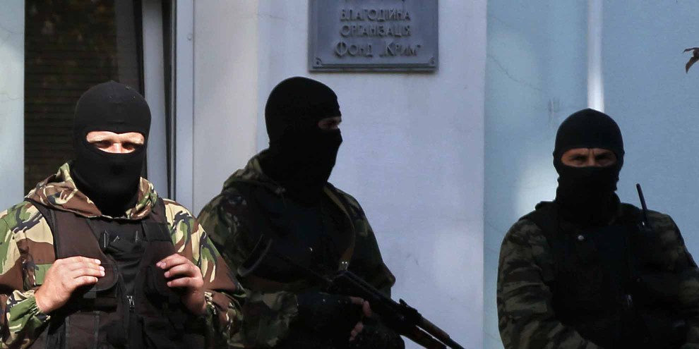 Des hommes armées devant l'entrée du conseil (mejlis) du peuple tatar de crimée. © MAX VETROV/AFP/Getty Images
