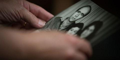 La femme d'un activiste politique disparu en 2013 tenant une photo de sa famille. © Amnesty International - Mark Esplin