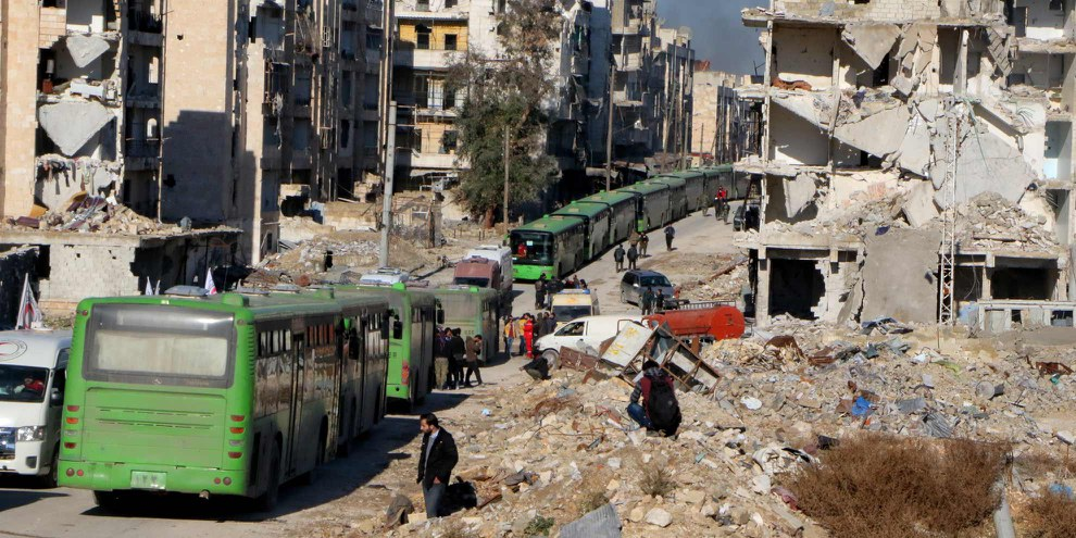 Un convoi de bus évacue des civils à Alep en décembre 2016. À Daraya, al Waer, Kefraya, Foua et dans l'est d'Alep, des milliers de personnes assiégées ont finalement été contraintes de laisser leurs maisons derrière elles dans le cadre des accords de «réconciliation». © Ibrahim Ebu Leys/Anadolu Agency/Getty Images
