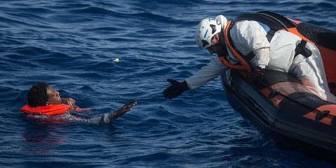 Un membre de l'équipage de Migrant Offshore Aid Station (MOAS) tend la main à un homme pour l'aider à rejoindre une embarcation de sauvetage © Chris McGrath/Getty Images