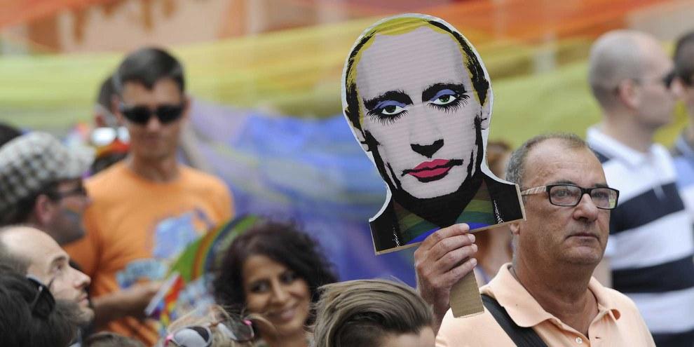"""L'idée semée par la Russie, selon laquelle les droits des LGBTI sont des """"valeurs occidentales"""" à rejeter, influence d'autres pays de la région, comme le Bélarus, l'Arménie, le Kazakhstan et le Kirghizistan. Sur la photo, un participant à la Rainbow Pride de Bratislava, en Slovaquie, brandit le portrait remanié du président russe Vladimir Poutine. © SAMUEL KUBANI/AFP/Getty Images"""