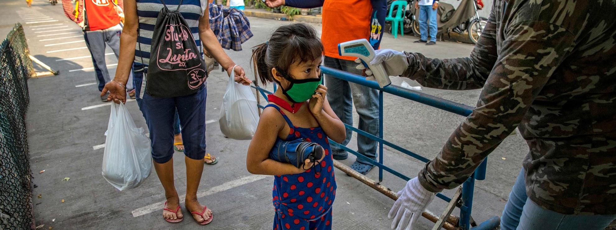 Nessuna eccezione: prima di entrare nella baraccopoli di Manila, questa bimba deve farsi misurare la febbre. A inizio aprile il presidente Rodrigo Duterte ha ordinato che le forze dell'ordine possono sparare ai residenti sorpresi a violare le norme della quarantena.  © Ezra Acayan/Getty Images