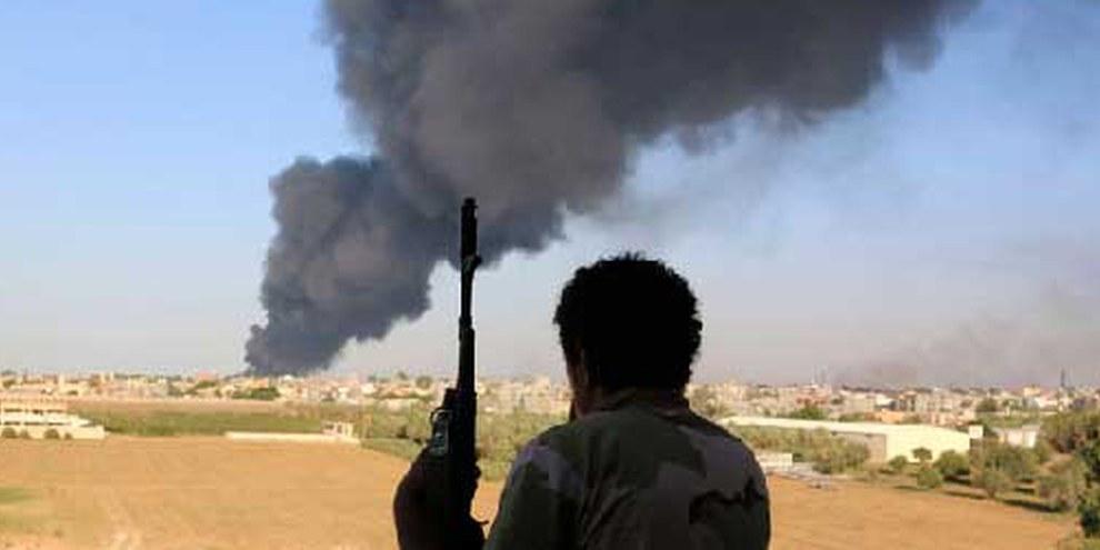 Un combattente della milizia Zintan osserva l'impatto di missili a Tripoli. © REUTERS/Hani Amara