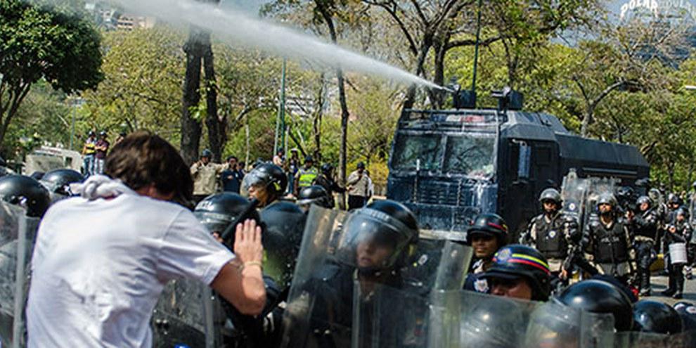 Le forze di sicurezza usano gli idranti contro i manifestanti a Caracas. | © Carlos Becerra